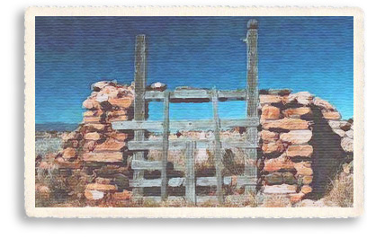 An old wooden gate set between stone pillars still guards the old cemetary at Gallisteo, New Mexico, just a few miles off the Turquoise Trail near the Garden of the Gods red rocks formation.